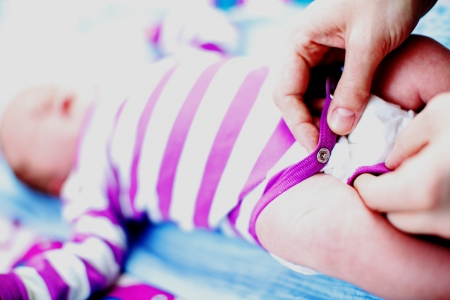 Closeup view of a young mother buttoning up a newborn infants playsuit after changing the baby diapers or nappies Stock Photo - 17458076