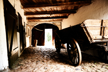 Wooden farm cart parked inside a large barn or stables on cobblestones Imagens - 27770921