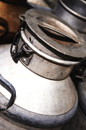 steel  milk: Closeup detail of an old steel milk container or urn with a removable lid used to transport fresh milk in a dairy