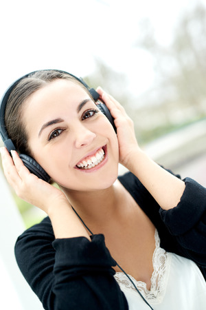 beaming: Smiling happy woman listening to music on a set of stereo headphones beaming with enjoyment and pleasure as she looks at the camera