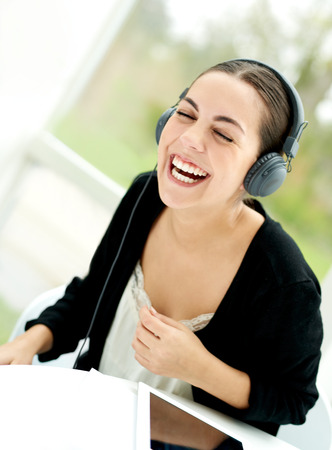 hilarity: Joyful young woman laughing as she listens to music on stereo headphones while sitting relaxing at home