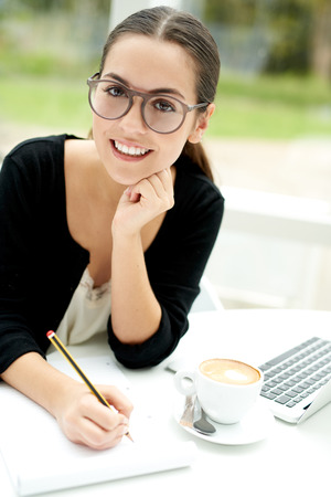 Smiling attractive young female student wearing eyeglasses sitting doing e-learning on a laptop computer writing notes for her classes
