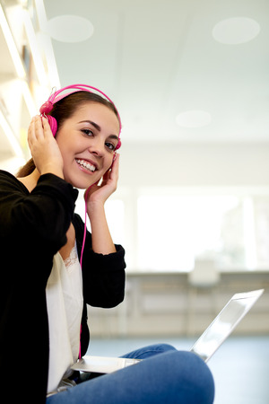 podcast: Young woman sitting outdoors listening to music on stereo headphones with her laptop balanced on her knees as she turns to smile at the camera