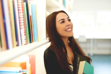 Mujer joven feliz soñando con sus estudios y posteriores oportunidades en la vida de pie juntando un libro contra su pecho junto a una estantería llena mirando hacia arriba con una sonrisa feliz Foto de archivo - 40563268