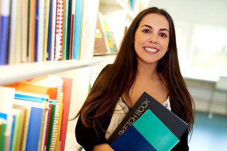 biblioteca: Estudiante de arte joven feliz en la biblioteca de la universidad de pie junto a una estantería llena de libros con un cuaderno de bocetos estrechó en sus brazos sonriendo a la cámara Foto de archivo