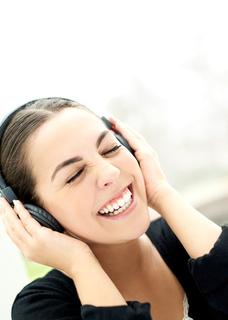vivacious: Vivacious young woman enjoying her music laughing as she holds her headphones to her ears, close up of her face with her eyes closed in bliss