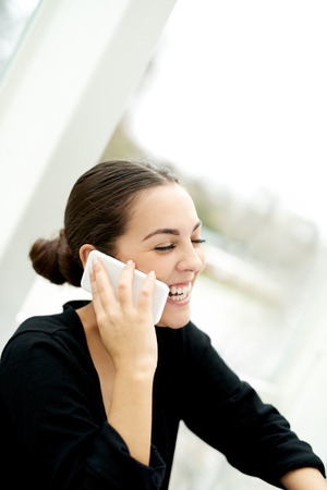 chats: Joyful young woman chatting on her mobile phone laughing as she listens to the conversation, side view seated indoors