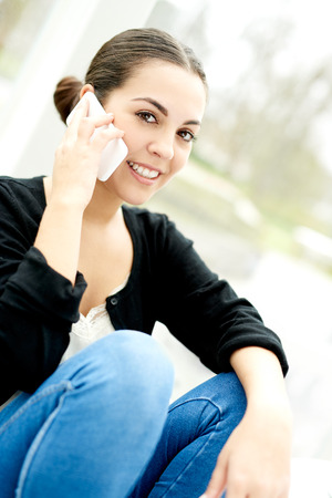 knees up: Young woman taking a call on her mobile phone sitting relaxing at home with her knees up looking at the camera with a smile Stock Photo