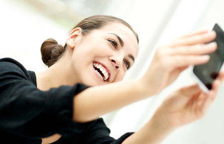 vivacious: Vivacious woman taking her selfie posing for the camera on her mobile phone with a beaming smile Stock Photo