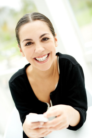beaming: Joyful young woman smiling at the camera with a beaming smile as she sits holding her mobile phone in her hands