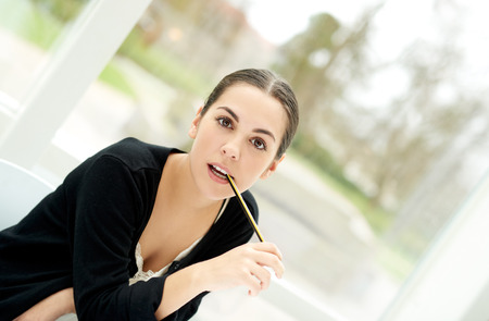 Intense young businesswoman sitting staring expectantly at the camera with her pen to her mouth, high angle in front of a view window