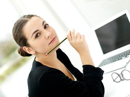 hipótesis: Atractivo joven empresaria estilo que se sienta en su escritorio con una computadora portátil y su lápiz elevado a la barbilla mirando a la cámara con una expresión seria