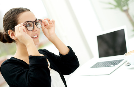 Young businesswoman adjusting her glasses as she prepares to start working on her laptop computer on her desk