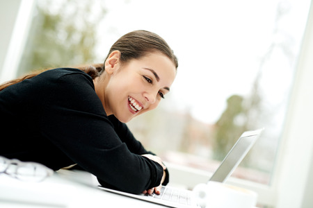 Young woman laughing in amusement and pleasure as she reads her laptop computer while relaxing at home with a cup of coffee, side view, natural expression, high key