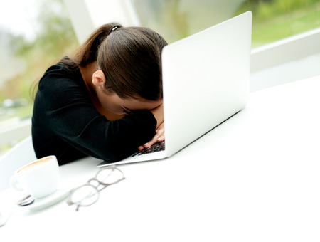 Despondent businesswoman leaning over her laptop computer with her head resting on the keyboard as she sits in the office