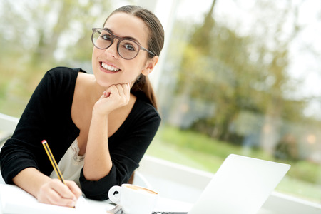 leans on hand: Thoughtful young businesswoman wearing fashionable glasses sitting working on paperwork looking at the camera with a smile