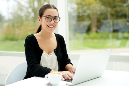 telecommuting: Friendly young woman working on a laptop outdoors on her patio looking up to give the camera a warm smile