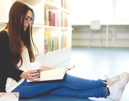 Young woman scholar relaxing with her books sitting stretched out on the floor in the university library doing research while enjoying takeaway coffee Imagens