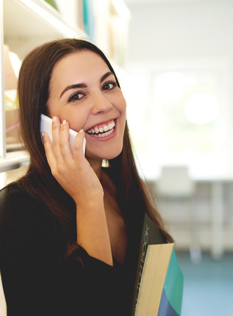 socialising: Young woman chatting on a smart phone glancing across at the camera with a happy beaming smile as she holds a large text book in her hands Stock Photo