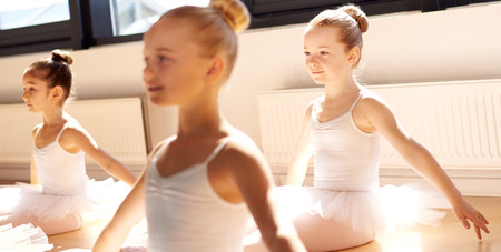 Three pretty young girls in ballet class sitting on the floor in a graceful pose in the white tutus in the warm sunshine