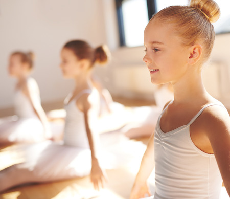 Close up side view of the face of a cute pretty little blond ballerina smiling in class as she practices her poses with her classmates in a warm bright ballet studio photo