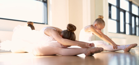 ballet ni�as: Little Ballet Girls Doing a Stretching Warm Up Exercise Inside the Studio Before their Dance Practice.