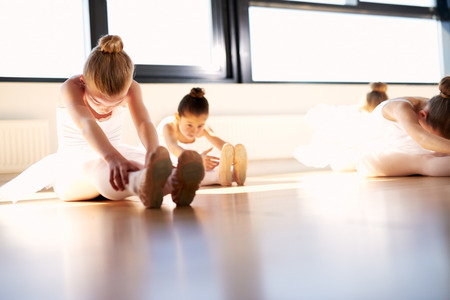 sit on studio: Little Ballet Girls Doing a Sit and Reach Warm-up Exercise for Body Stretching Inside the Studio, Prior to their Dance Rehearsal. Stock Photo