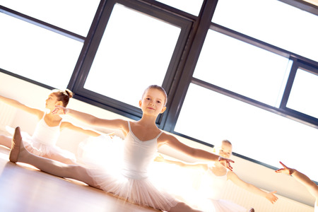 tilted view: Pretty little ballerina in ballet class sitting on the wooden floor in a bright sunlit dance studio practising her poses , low angle tilted view