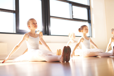 ballet child: Dedicated group of young ballerinas sitting on a wood floor in a warm bright ballet studio practising in the white tutus, low angle view Stock Photo