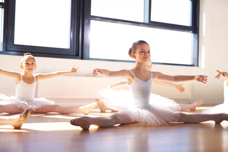 Pretty Young Ballerinas in White Tutus, Sitting on the Floor and Stretching Arms and Legs as Warm Exercise.