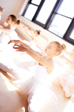 legs open: Pretty Little Ballet Girl in White Tutu, Doing a Stretching Exercise, with Legs Open and Arms Forward, Inside the Studio with her Other Classmates.
