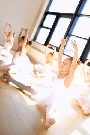 legs open: Cute Young Ballet Girls in a Training Exercise, with Legs Open and Arms Up While Sitting on the Floor, Inside the Dance Studio