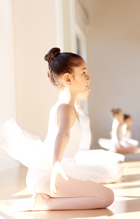 arm extended: Side View of an Attentive Young Pretty Ballerina Girl During the Ballet Training, Sitting on her Ankle with Arms on her Side Away from her Body. Stock Photo