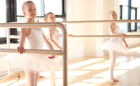 ballet bar: Group of young ballerinas in training at a classical ballet studio standing practicing together at the bar