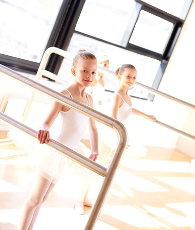 dance studio: Group of pretty aspiring young ballerinas practicing at the bar in a bright sunny ballet studio with one little girl looking at the camera with a smile