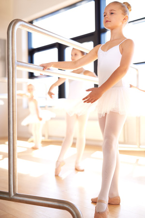 dance bar: Graceful young girl practicing her ballet in a classical dance studio standing posing at the bar in her white tutu