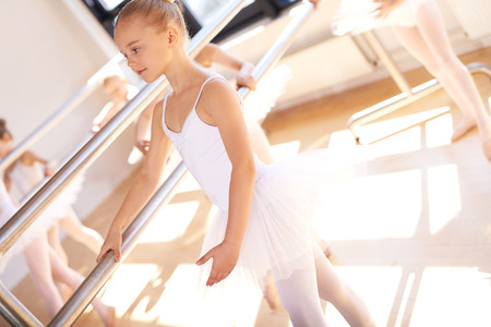 ballet bar: Young ballerina in ballet school practicing at the bar with her classmates in her white tutu, close up view