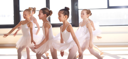 Group of young ballerinas performing a choreographed ballet as they train together at a ballet studio