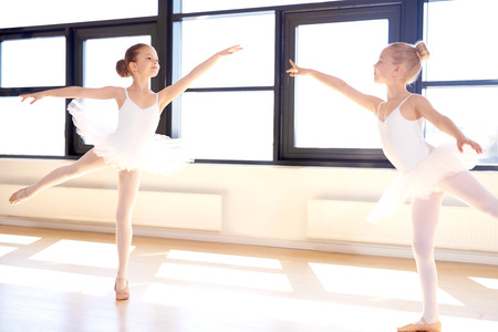 Two graceful little girls practicing a choreographed ballet in a classical ballet studio as they fulfil their dreams to become accomplished ballerinas