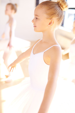 Close up Smiling Pretty Little Ballet Girl in White Tutu at the Dance Training Inside the Studio.