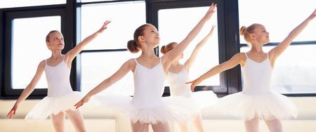 ballet: Bailarinas jovenes que practican un baile coreografiado todo lloviendo sus brazos al unísono graciosa durante la práctica en una escuela de ballet