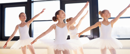 Young ballerinas practicing a choreographed dance all raining their arms in graceful unison during practice at a ballet school