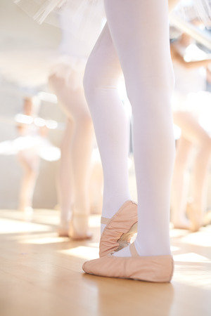 ballet bar: Young ballerina wearing pink satin pointe shoes in class as they stand at the bar practising their positions during training Stock Photo