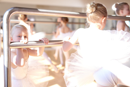 dance bar: Little White Ballerinas Doing a Stretching Exercise Using a Ballet Horizontal Bar at the Dance Studio.
