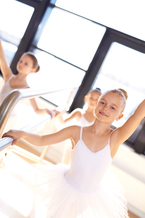barre: Pretty smiling young ballerina in training using the bar in the ballet school studio to practice her positions and balance with a group of young girls