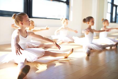 taniec: Pretty młodych dziewczyn, ubrany w białą Tutus, siedząc na podłodze w studio mając Szkolenia dla balet.