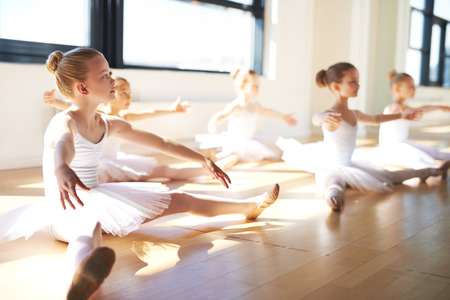 Pretty Young Girls, Wearing White Tutus, Sitting on the Floor at the Studio While Having a Training for Ballet Dance. Stock Photo