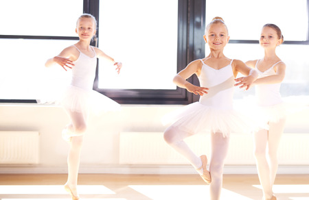 Group of pretty graceful young ballerinas practicing pirouettes in their white tutus during a dance class in a classical ballet school