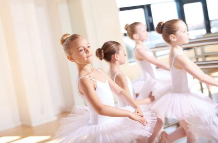 ballet niñas: Lindas pequeñas bailarinas vestir de blanco Tutus, Practicar su danza Dentro del Estudio Durante su Ballet Class. Foto de archivo