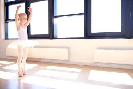 優雅な腕の中で立っているバレリーナになりトレーニング少女発生彼女の白いチュチュの位置と明るい太陽に照らされたバレエ スタジオでピンクの